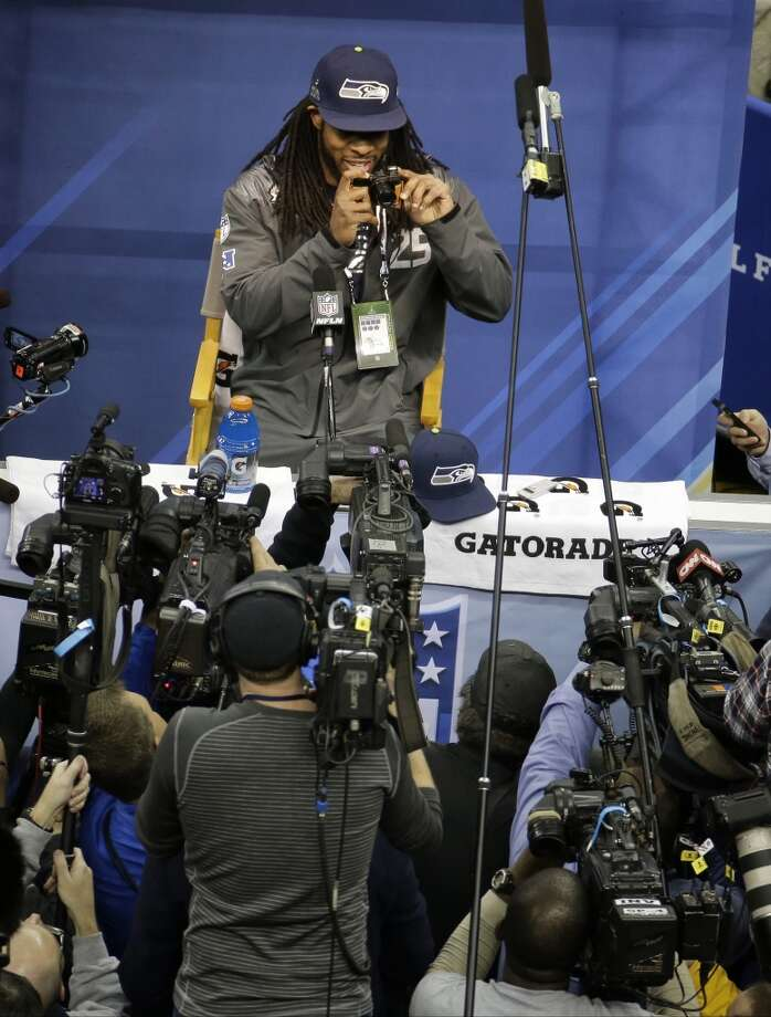 Seattle Seahawks' Richard Sherman takes pictures during media day for the NFL Super Bowl XLVIII football game Tuesday, Jan. 28, 2014, in Newark, N.J. (AP Photo/Charlie Riedel) Photo: Charlie Riedel, AP