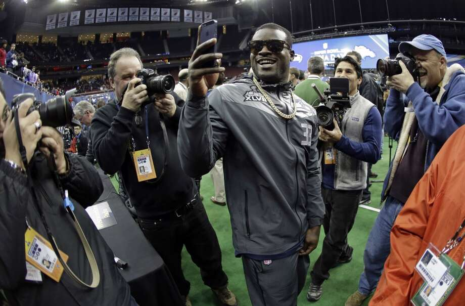 Seattle Seahawks' Christine Michael takes pictures during media day for the NFL Super Bowl XLVIII football game Tuesday, Jan. 28, 2014, in Newark, N.J. (AP Photo/Charlie Riedel) Photo: Charlie Riedel, AP