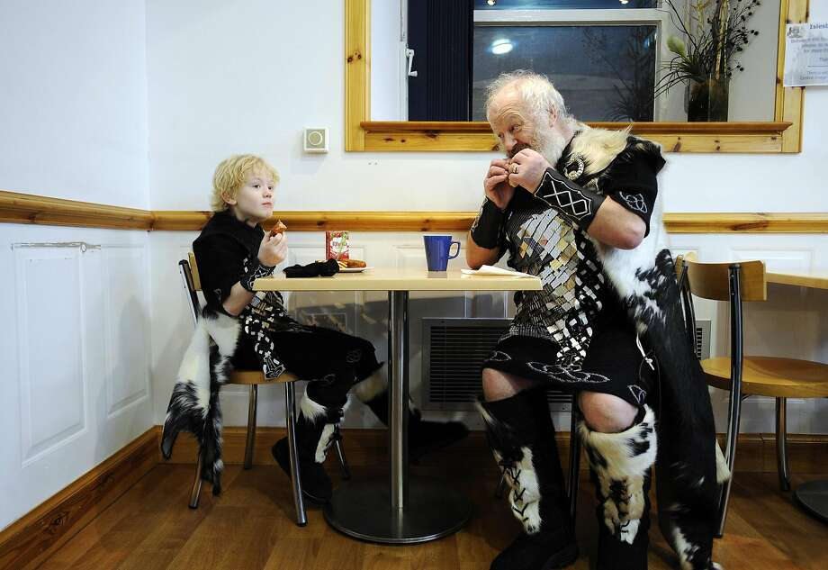 Not with your fork, with your fingers, son! Like this: A guizer (costumed Norseman) shows a neophyte proper Viking manners during breakfast at Helly Aa festival in Lerwick, Shetland Islands. Photo: Andy Buchanan, AFP/Getty Images