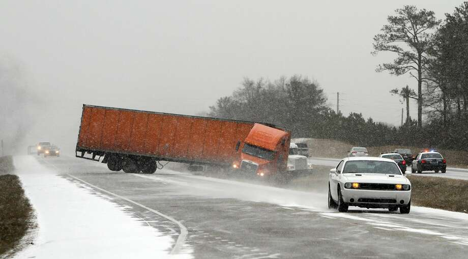 Snow in the land of cotton: A tractor-trailer jackknifes off the highway while trying to avoid another wrecked truck as snow begins to accumulate on I-65 in Clanton, Ala. Alabama drivers rarely have to contend with ice and snow on the road. Photo: Butch Dill, Associated Press