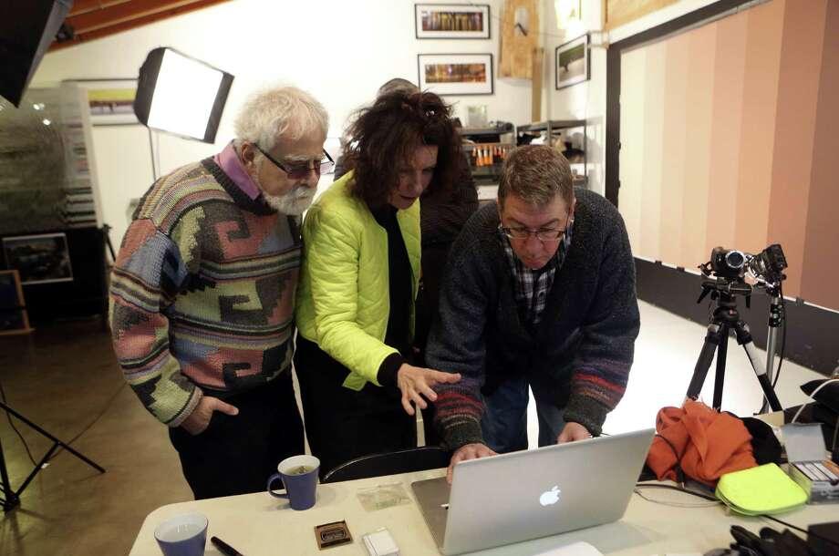 David Rubin (from left), French video artist Sylvie Blocher and Ansen Seale view footage Blocher filmed in Seale's studio. Photo: Helen L. Montoya / San Antonio Express-News / SAN ANTONIO EXPRESS-NEWS