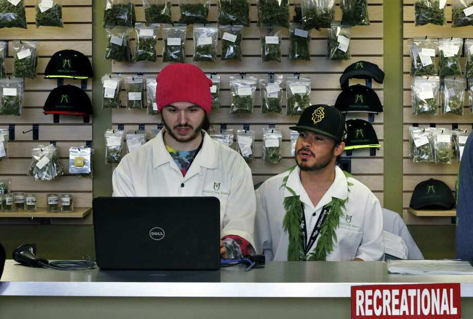 "Dude, what's the price of Mendocino Mirage, again? David Marlow (right) and Chris Broussard work the sales counter inside the Medicine Man marijuana retail store in Denver. Colorado began retail marijuana sales on Jan. 1, a day some are calling ""Green Wednesday."" Photo: Brennan Linsley / Associated Press / AP"