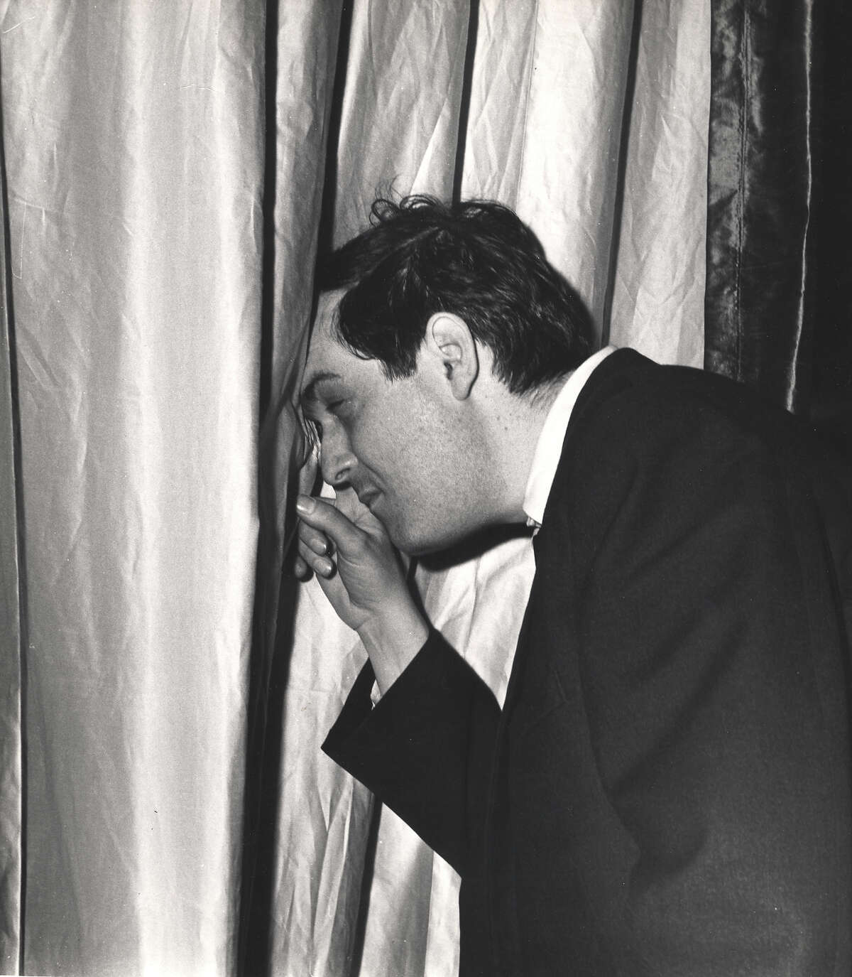 American film director Stanley Kubrick peeks through a curtain on the set of his film 'Dr. Strangelove, Or How I Learned to Stop Worrying and Love the Bomb' (1964) England, early 1963.