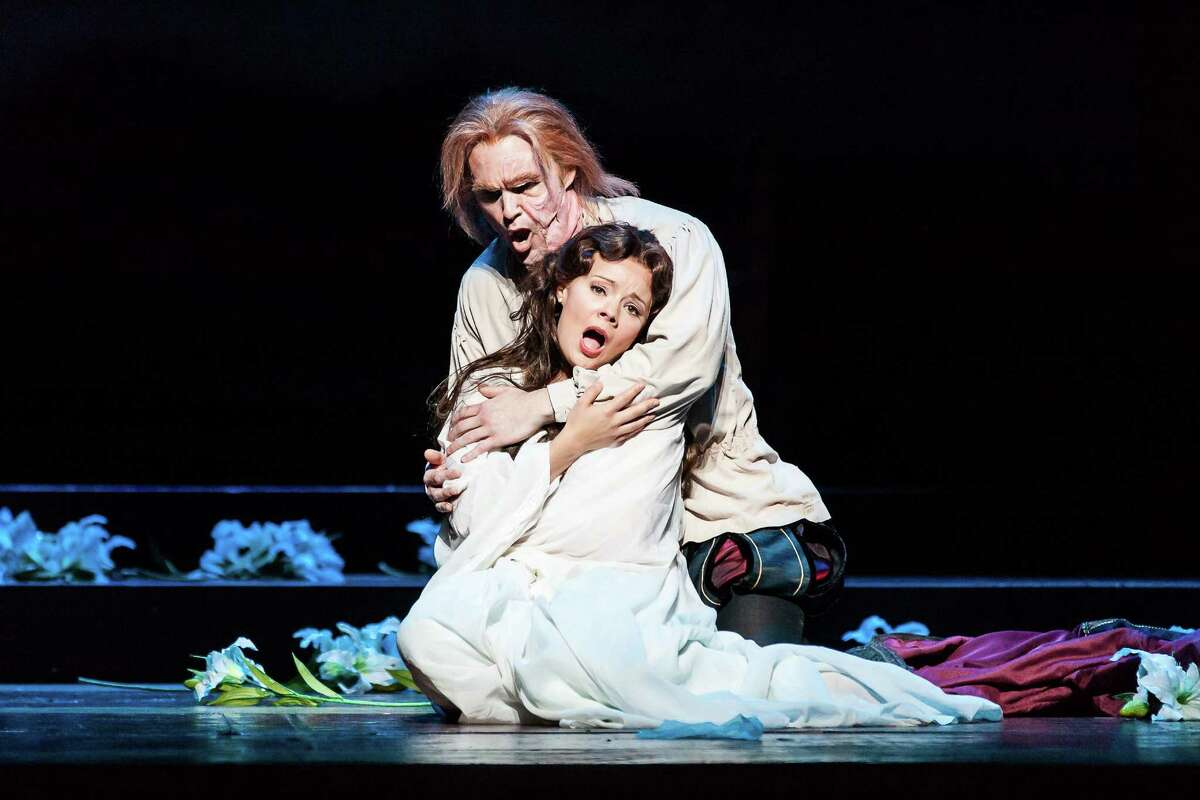 """Rigoletto, played by Ryan McKinny, consoles his daughter, Gilda, played by Uliana Alexyuk, in Houston Grand Opera's staging of Giuseppe Verdi's """"Rigoletto."""""""