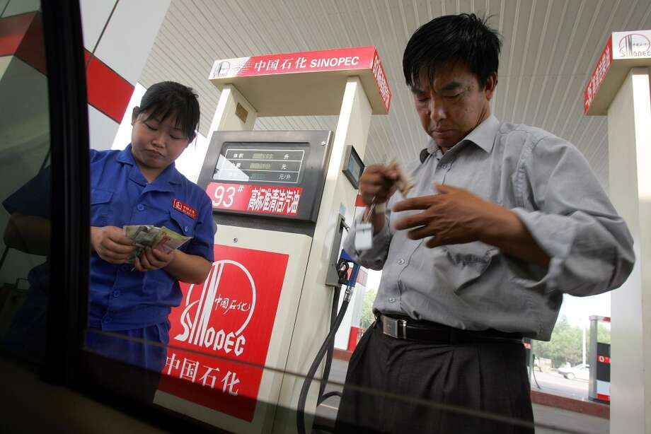 Sinopec -- China-based integrated oil and gas company  Share price change: down 14% Market cap: $88.2 billion 2013 market cap rank: 10 2012 market cap rank: 11  [Photo: A Sinopec gas station attendant (left) checks cash paid by a taxi driver (right) in Beijing in June 2005.] Photo: FREDERIC J. BROWN, AFP/Getty Images