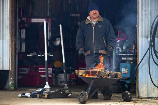 "Galdino Romero stands by a fire to stay warm outside his tire shop on Aldine Westfield Tuesday, Jan. 28, 2014, in Spring. ""I have a heater inside, but I like to be out here,"" Romero said. ""The fire is good."" Photo: Brett Coomer, Houston Chronicle / © 2014 Houston Chronicle"