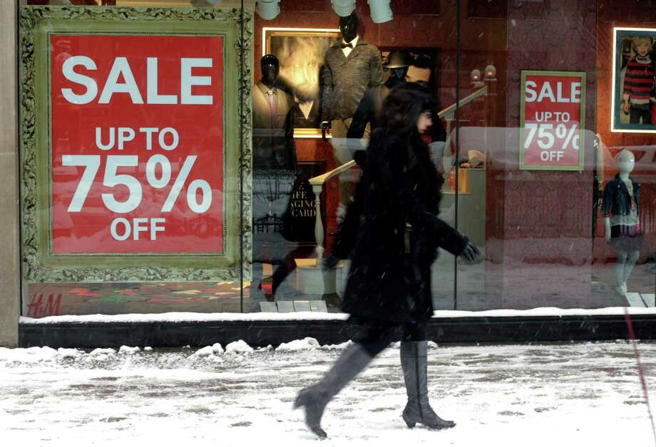 In this Jan 2, 2014 photo, a pedestrian passes by sale signs on a store front window in Chicago. The Conference Board releases the Consumer Confidence Index for January, on Tuesday, Jan. 28, 2014. (AP Photo/Kiichiro Sato) ORG XMIT: NYBZ131 Photo: Kiichiro Sato / AP