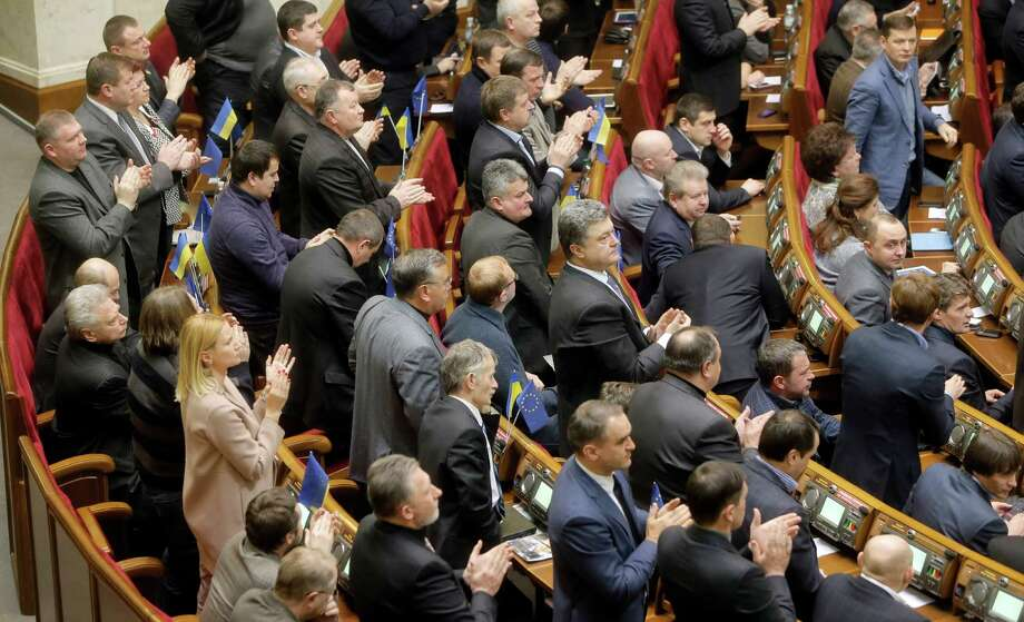 Ukrainian lawmakers applaud after voting during a parliamentry session in Kiev, Ukraine, Tuesday, Jan. 28, 2014. In back-to-back moves to try and resolve Ukraine's political crisis, the prime minister submitted his resignation Tuesday and parliament repealed anti-protest laws that had set off violent clashes between protesters and police. (AP Photo/Efrem Lukatsky) Photo: Efrem Lukatsky, STF / AP