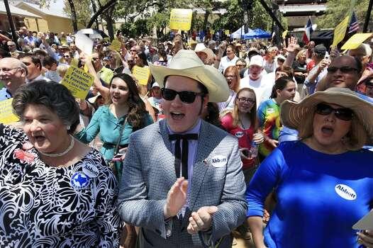 Abbott supporters Maggie Wright, left, Chandler Wahrmund, and his mother, Laralee List Wahrmund, cheer Abbott's announcement July 14, 2013. Photo: Edward A. Ornelas, San Antonio Express-News