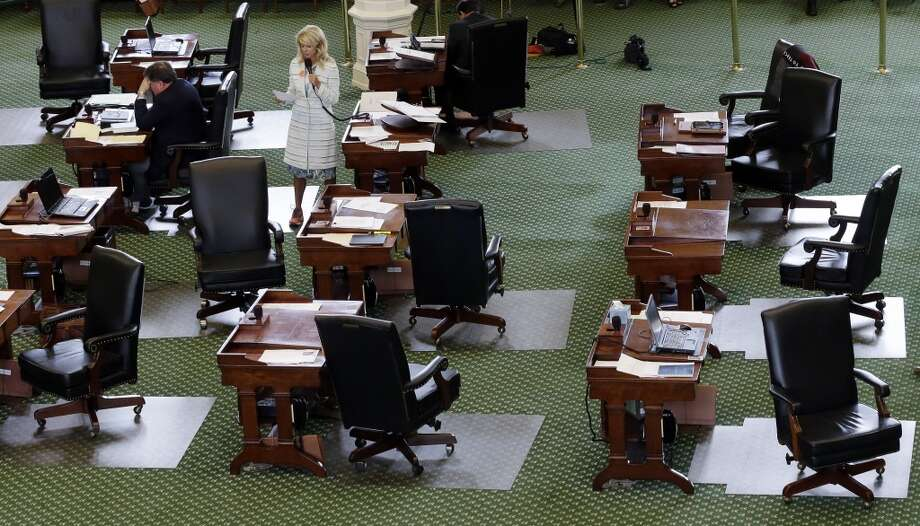 Davis stands on a nearly empty Senate floor as she filibusters in an effort to kill an abortion bill June 25, 2013, in Austin. The bill would ban abortion after 20 weeks of pregnancy and force many clinics that perform the procedure to upgrade their facilities and be classified as ambulatory surgical centers. Photo: Eric Gay, Associated Press