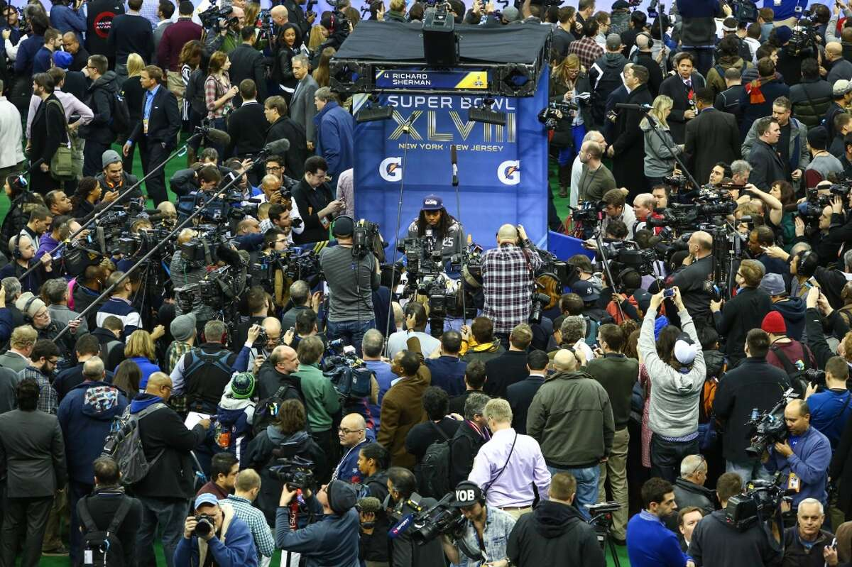 Seahawks player Richard Sherman is surrounded by cameras and reporters during Super Bowl Media Day on Tuesday, January, 28, 2014 at the Prudential Center in Newark, NJ. During Media Day players are available for for interviews and photos. The event takes on a circus atmosphere as players interact with reporters and celebrities. (Joshua Trujillo, seattlepi.com)