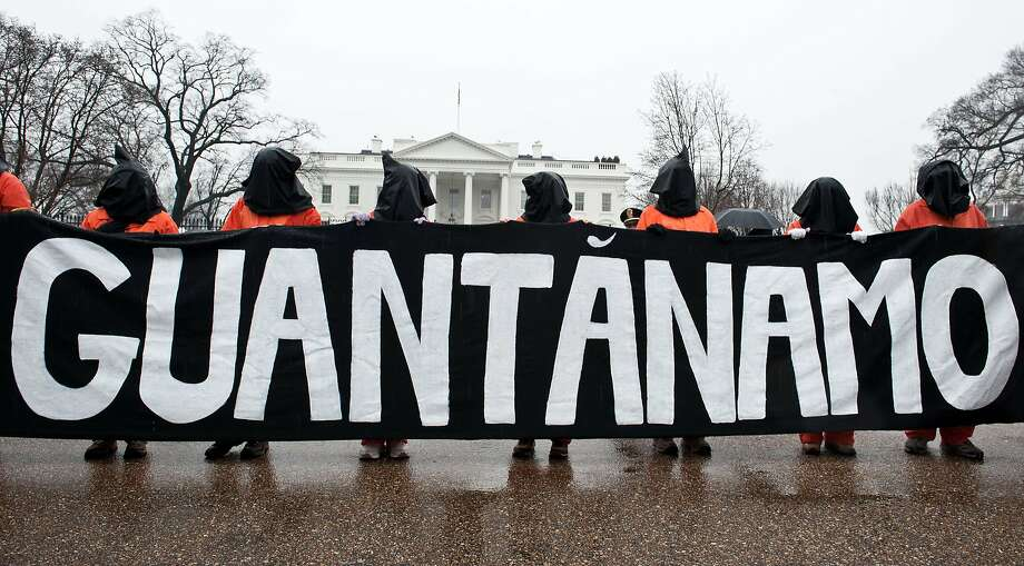 Protesters in front of the White House hold a banner calling for the U.S. to close the detention center at Guantanamo Bay. Photo: Nicholas Kamm, AFP/Getty Images