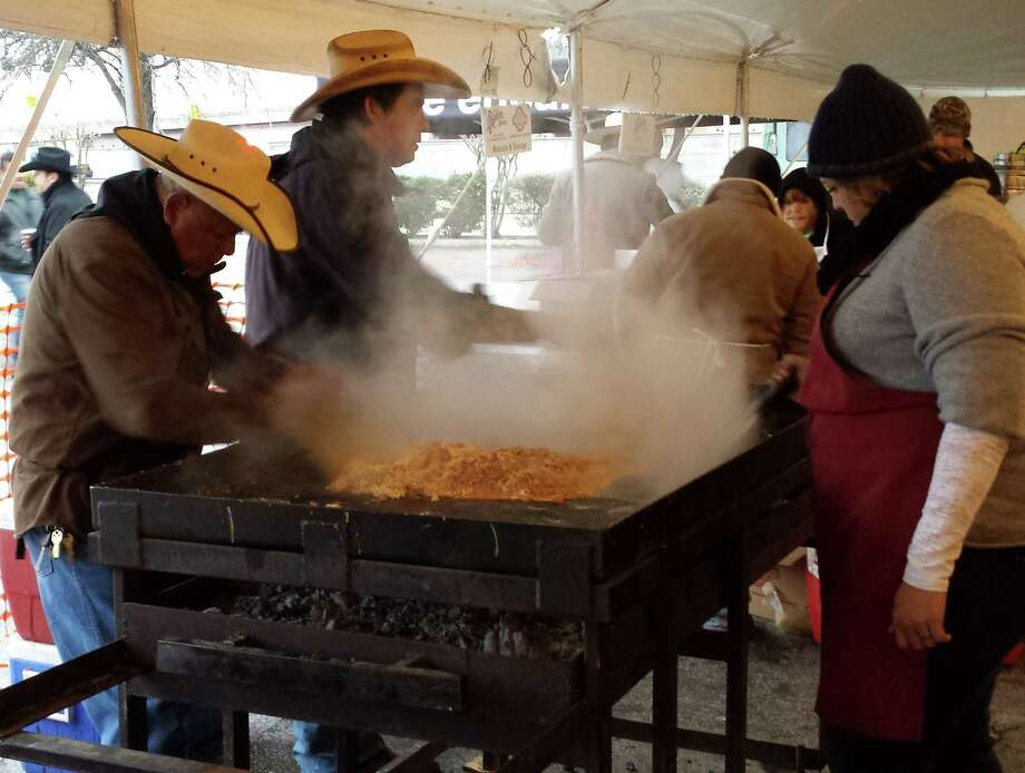 Volunteers scramble eggs and prepare breakfast tacos for some 20,000 hungry souls who braved below-freezing temperatures to take part in Friday's Cowboy Breakfast at Cowboys Dancehall. The unforgiving temperatures may have cut attendance by more than half, but many in the crowd said they were glad they came.