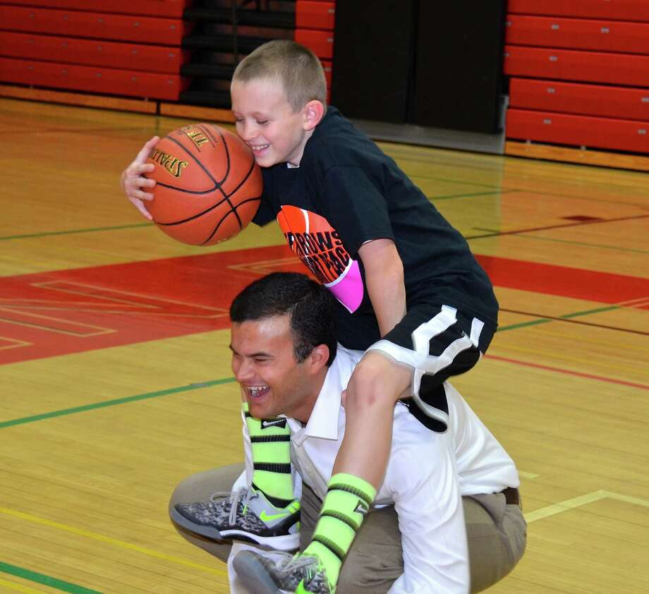 "Gavin Bramwit climbs up on Conn State Senator Art Linares's back for some extra height during the fundraising event, ""Free Throws for Full Court Peace,"" on Sunday, Jan 26, 2014, at New Canaan High School. Photo: Jeanna Petersen Shepard / New Canaan News Freelance"