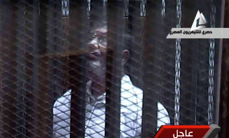 Egyptian state TV carried this image of  toppled President Mohammed Morsi standing inside a glass-encased metal cage in a courtroom in Cairo on Tuesday, Morsi was separated from other defendants. Photo: Uncredited, TEL / Egyptian State TV