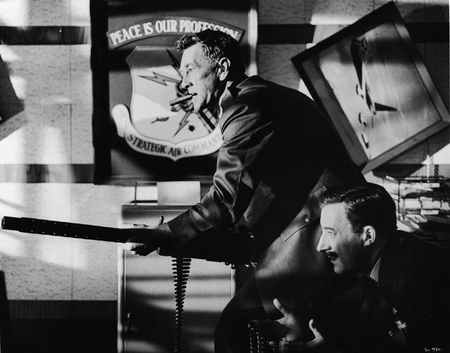 American actor Sterling Hayden , as General Jack Ripper, fires a machine gun while English born actor Peter Sellers, as Group Captain Lt. Mandrake, feeds him the bullets in a still from the Stanley Kubrick directed film, 'Dr. Strangelove: Or How I Came to Stop Worrying and Love the Bomb.' Photo: Columbia TriStar, Getty Images