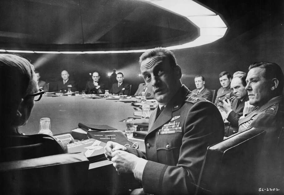 American actor George C Scott looks over his shoulder while sitting at a round table with other officials in a still. Photo: Columbia Pictures, Getty Images