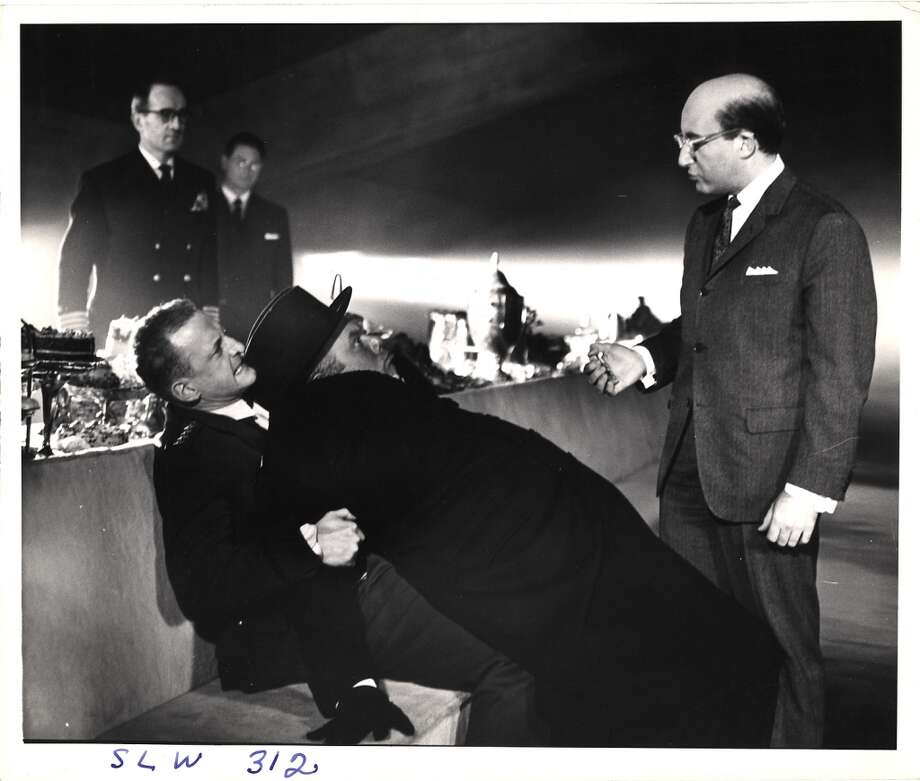 British actor Peter Sellers (1925 - 1980) (as President Merkin Muffley) (right) talks to actor Peter Bull (1912 - 1984) (as Alexi de Sadesky) (center), who is restrained by American actor George C. Scott (1927 - 1999) (as General Buck Turgidson) (left), in the War Room set of the movie 'Dr. Strangelove, Or How I Learned to Stop Worrying and Love the Bomb' (directed by Stanley Kubrick) at Shepperton Studios, Shepperton, England, 1963 Photo: Getty Images