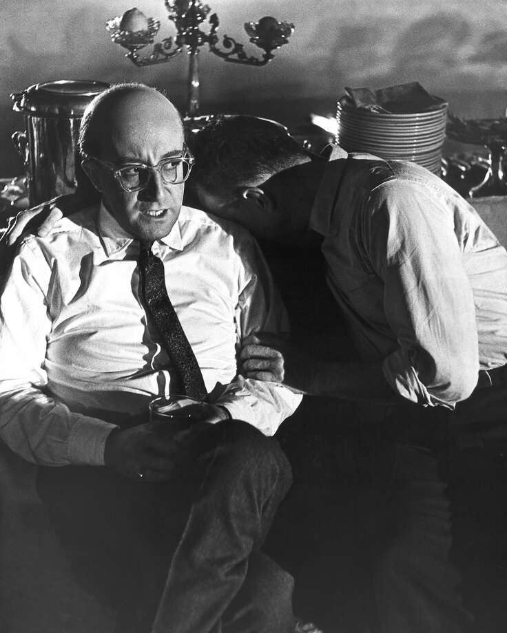 Peter Sellers (1925-1980), British actor, with a bald head, and a man who rests his head on Sellers' left shoulder, in a publicity still issued for the film, 'Dr Strangelove or: How I Learned to Stop Worrying and Love the Bomb', 1964. The black comedy, directed by Stanley Kubrick (1928-1999), starred Sellers as 'Group Captain Lionel Mandrake'. Photo: Getty Images