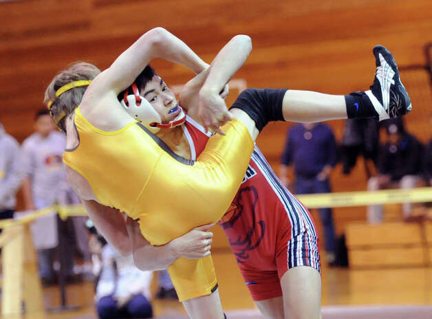 At left, Brunswick's Andrew Hennessy (light yellow outfit) goes up against Brandon Aguda (dark red outfit) of Greenwich in the 106 pound weight class match that Aguda won during high school wrestling match be