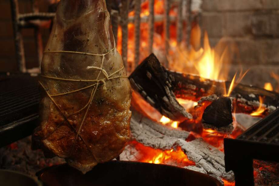 Lamb leg a la ficelle hanging over the wood-fired oven. Photo: Eric Luse, The Chronicle