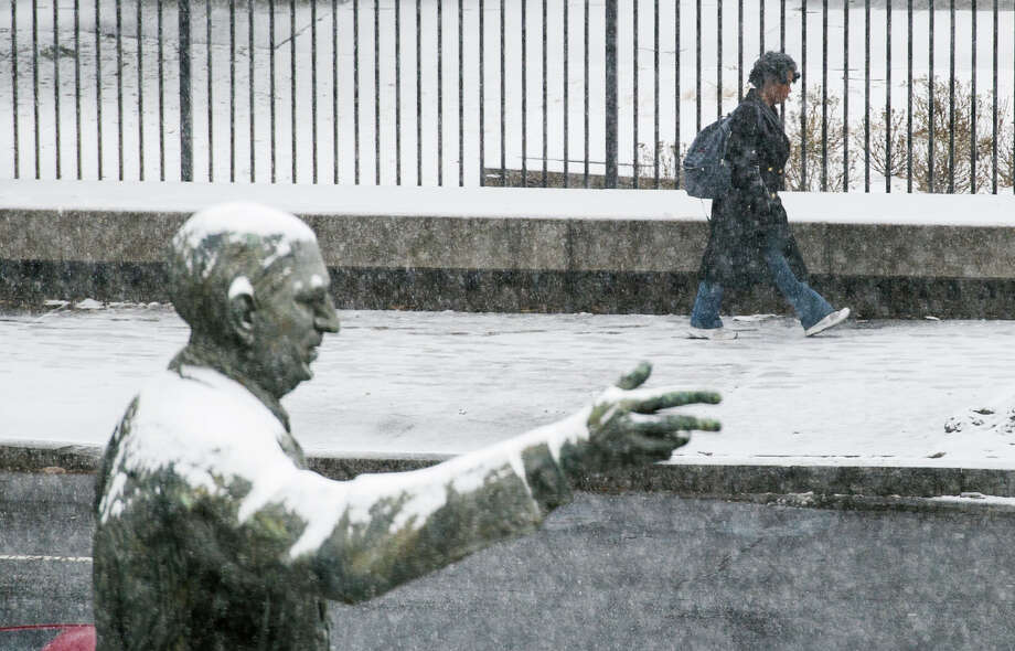 The snow covered statue of late Georgia Governor and U.S. Sen.Richard B. Russell points the direction for a pedestrian as she makes her way past the state capitol while snow begins to accumulate Tuesday, Jan. 28, 2014, in Atlanta. (AP Photo/John Amis) Photo: John Amis / FR69715 AP