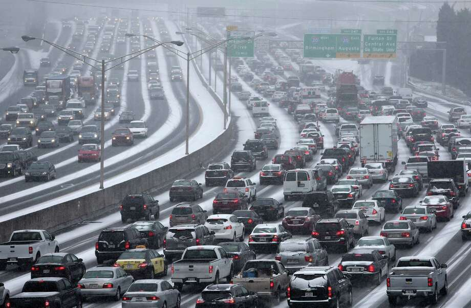 Traffic inches along the connector of Interstate's 75 and 85 as snow blankets Metro Atlanta on Tuesday afternoon, Jan. 28, 2014 as seen from the Pryor Street overpass.  Georgia Gov. Nathan Deal is preparing to declare a state of emergency as a winter storm coats the region with snow and ice. State transportation officials said a mass of commuters leaving downtown Atlanta at once created traffic jams on interstates and surface streets. (AP Photo/The Atlanta Journal-Constitution, Ben Gray) ORG XMIT: GAATJ601 Photo: BEN GRAY / The Atlanta Journal-Constitution