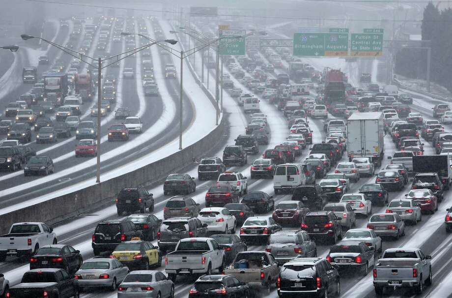 Traffic inches along in Atlanta, where a mass of commuters leaving downtown amid a winter storm led to traffic jams. About 3 inches of snow was expected in parts of Georgia. Photo: Ben Gray / Associated Press / The Atlanta Journal-Constitution