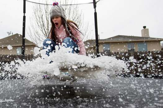 Eryn Garza bounces on a trampoline covered with slush from an overnight sleet storm Tuesday in Spring. Photo: Brett Coomer, Staff / © 2014 Houston Chronicle