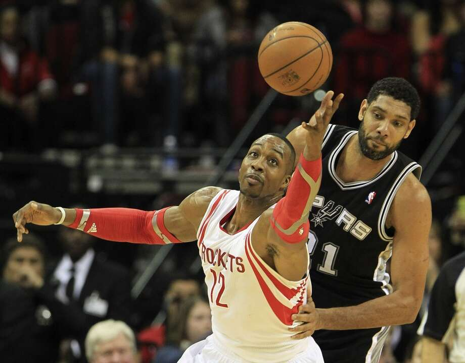 Rockets center Dwight Howard tries to track down a loose ball as Tim Duncan of the Spurs looks on. Photo: Karen Warren, Houston Chronicle