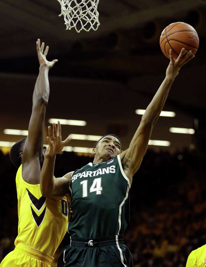 Michigan State guard Gary Harris, right, drives to the basket past Iowa center Gabriel Olaseni, left, during the first half of an NCAA college basketball game, Tuesday, Jan. 28, 2014, in Iowa City, Iowa. (AP Photo/Charlie Neibergall) ORG XMIT: IACN110 Photo: Charlie Neibergall / AP