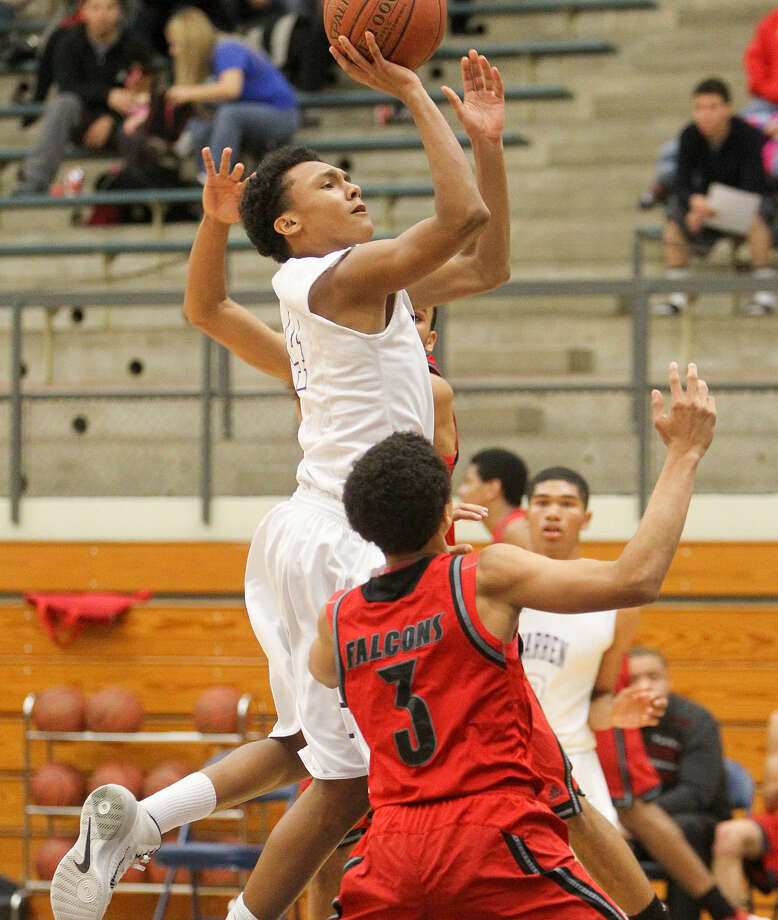 Warren's Isaiah Thorne shoots over Stevens' Aaron Williamson in the second quarter at Taylor Field House. Thorne, a freshman, scored 18 points in the Warriors' victory. Photo: Marvin Pfeiffer / Express-News / Express-News 2013