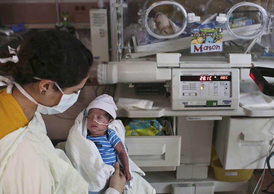 Michelle Rivas of Laredo holds son Mason Aguilar after feeding him donated breast milk at University Hospital. Photo: Lisa Krantz / San Antonio Express-News / San Antonio Express-News