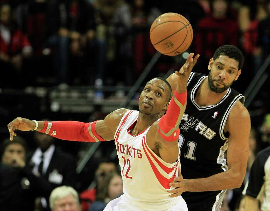 In a marquee matchup, Rockets center Dwight Howard gets to a loose ball ahead of Spurs veteran Tim Duncan. Photo: Karen Warren, Staff / © 2013 Houston Chronicle