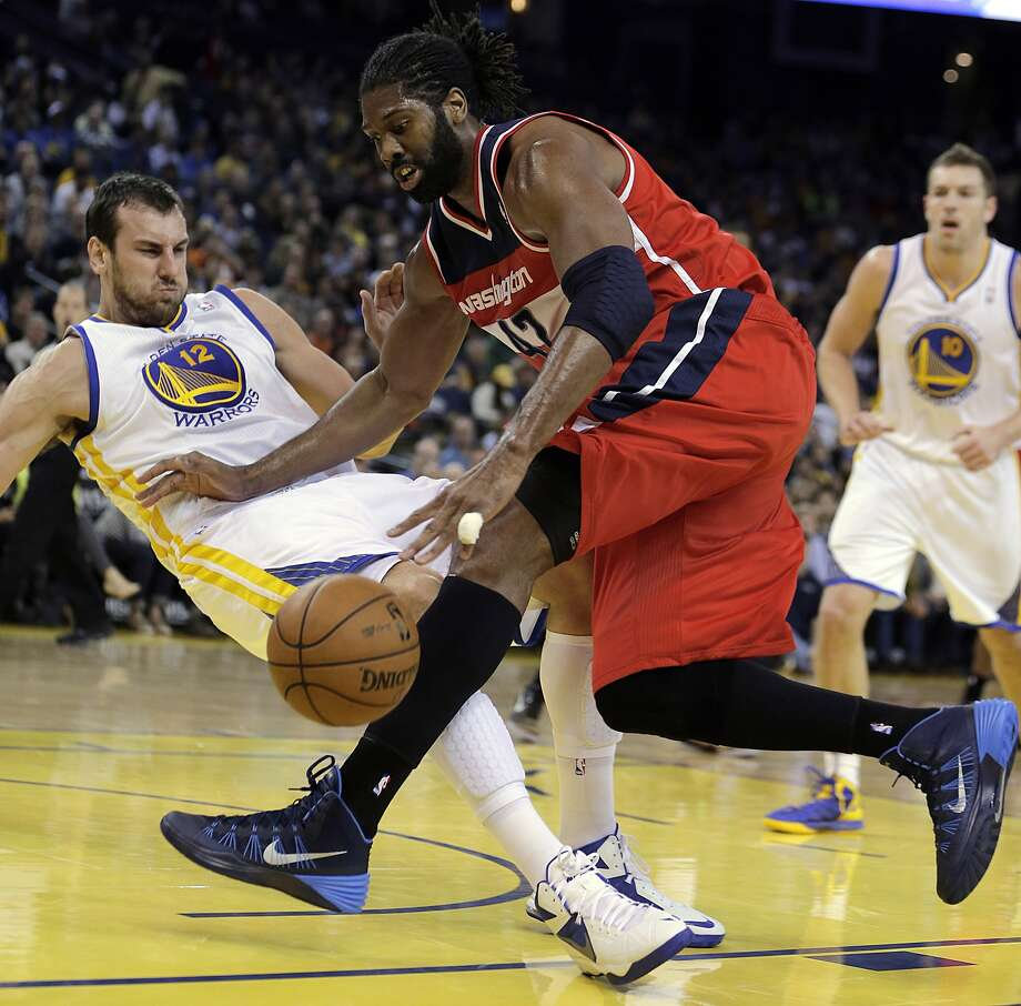 Washington's Nene (right) drives into the Warriors' Andrew Bogut. Photo: Ben Margot, Associated Press