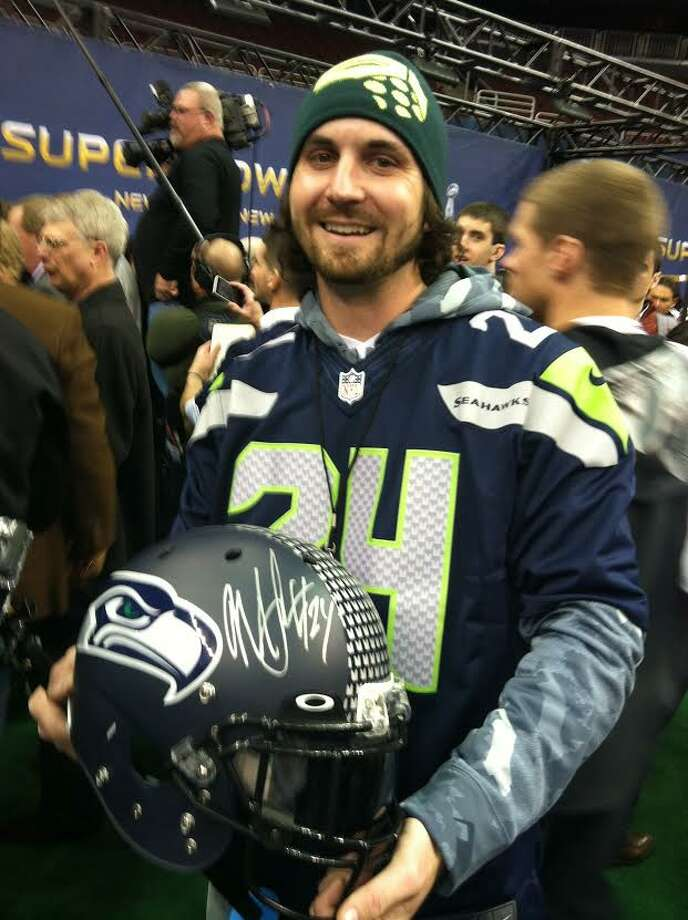 Seattle native Jordan Slack showing off the helmet Seahawks running back Marshawn Lynch autographed for him.
