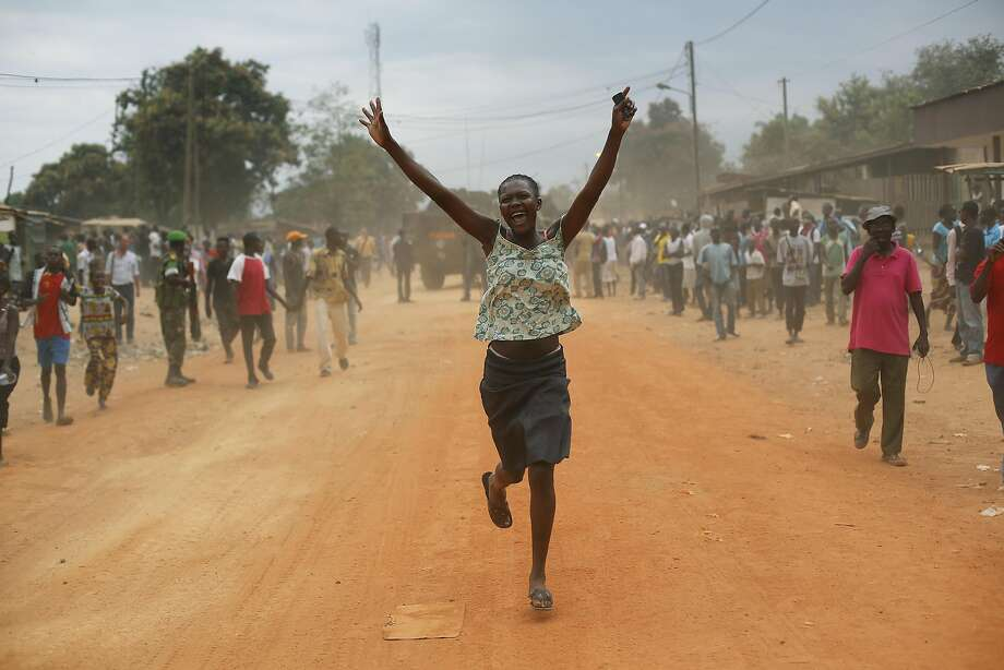 "Christian residents jubilate as Seleka Muslim militias evacuate the Kasai camp in Bangui, Central African Republic, Tuesday, Jan. 28, 2014, to relocate and join other Selekas at the PK11 camp. The departure of the fighters was greeted with screams of joy from the crowd of hundreds that gathered to watch them leave for another camp in northern Bangui. ""We are free! This is our new year!"" they shouted. Seleka became deeply unpopular after they killed and tortured civilians after seizing power in March 2013. Their leader Michel Djotodia stepped down as president earlier this month and went into exile in Benin. (AP Photo/Jerome Delay) Photo: Jerome Delay, Associated Press"