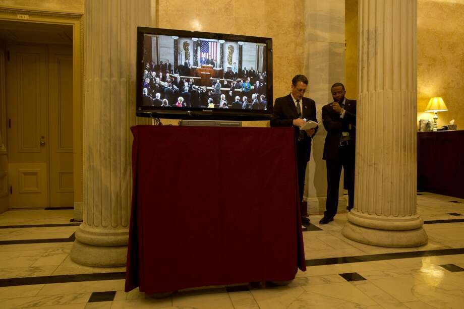 A television shows the speech live in the U.S. Capitol. (Jacquelyn Martin/Associated Press)