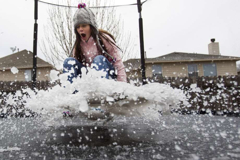 Eryn Garza bounces on a slush-covered trampoline from an overnight sleet storm Tuesday, Jan. 28, 2014, in Spring. ( Brett Coomer / Houston Chronicle ) Photo: Houston Chronicle