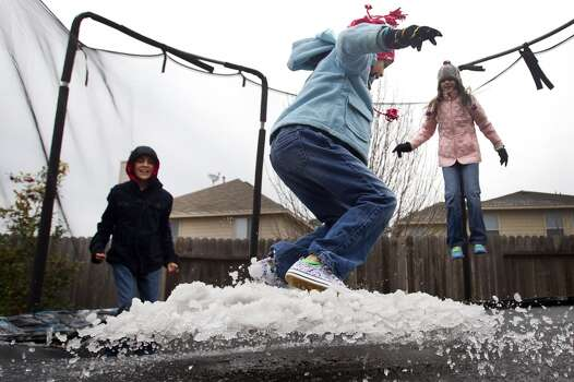 Emery Garza, center, bounces on a slush-covered trampoline from an overnight sleet storm with her brother, Zack, left, and sister, Eryn, Tuesday, Jan. 28, 2014, in Spring. ( Brett Coomer / Houston Chronicle ) Photo: Houston Chronicle