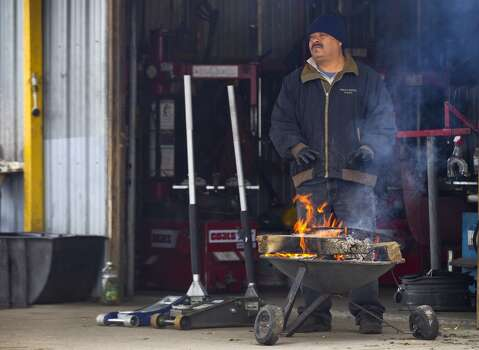 "Galdino Romero stands by a fire to stay warm outside his tire shop on Aldine Westfield Tuesday, Jan. 28, 2014, in Spring. ""I have a heater inside, but I like to be out here,"" Romero said. ""The fire is good.""( Brett Coomer / Houston Chronicle ) Photo: Houston Chronicle"