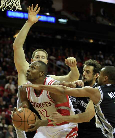 Houston Rockets center Dwight Howard (12) fights to get to the basket against San Antonio Spurs power forward Aron Baynes (16), Marco Belinelli (3) and Patty Mills (8) during the second half of an NBA game at Toyota Center,Tuesday, Jan. 28, 2014. Rockets beat the Spurs 97-90. Photo: Karen Warren, Houston Chronicle / © 2013 Houston Chronicle