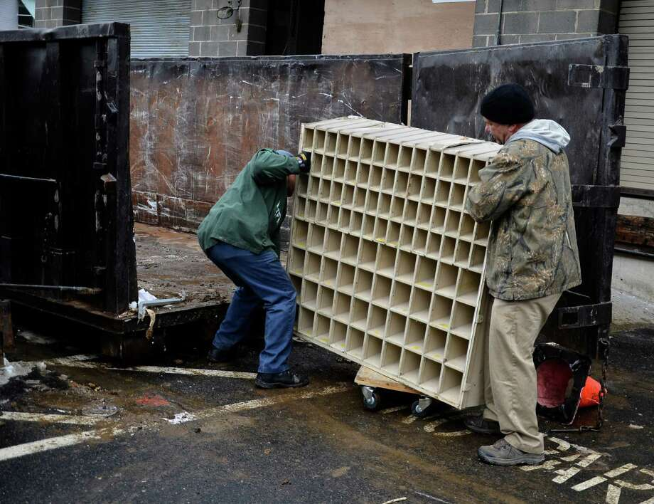 Two postal service employees throw a metal mailbox from New Canaan's old post office location - 2 Pine St. - into a dumpster behind the facility on Monday, Jan. 27, 2014. The brass doors of those boxes, however, have been sent to an asset management site, U.S. Postal Service spokesman Christine Dugas said. Photo: Nelson Oliveira / New Canaan News