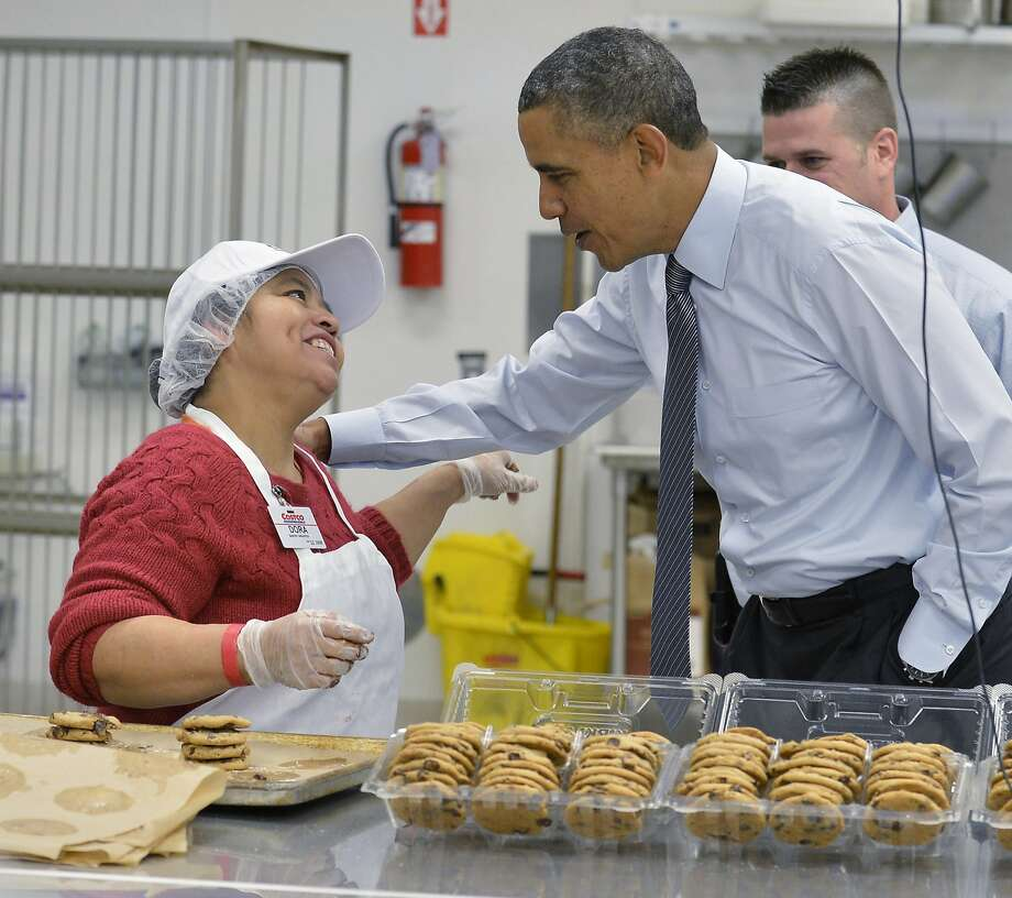 President Obama greets an employee in the bakery at a Costco store 