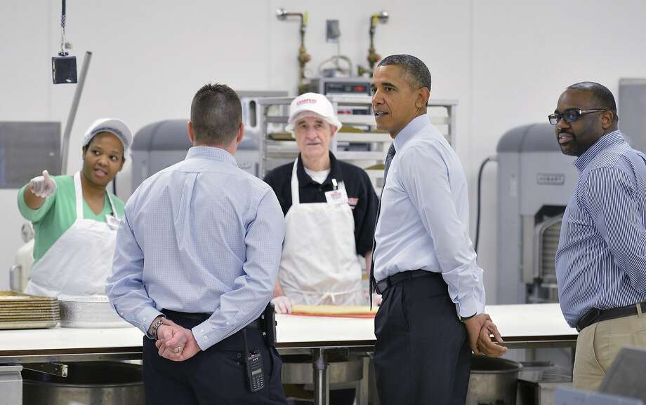 LANHAM, MD - JANUARY 29:  U.S. President Barack Obama (2nd R) visits with Costco bakers while he is escorted by Costco employees Ray Queved ( 2nd L) and Rickey Banner (R) during a tour of the store before speaking January 29, 2014 in in Lanham, Maryland.  Obama is beginning a two-day, four-state tour to promote policies outlined in his State of the Union speech and including raising the minimum wage.  (Photo by Mike Theiler-Pool/Getty Images) Photo: Pool, Getty Images