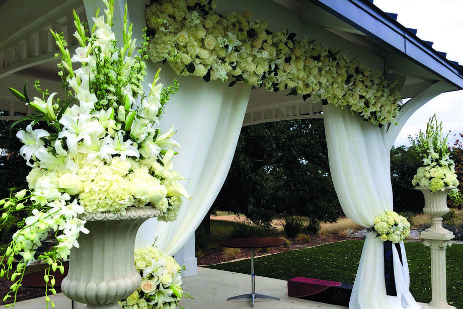 Floral Arrangements In Whites And Creams Add To The Elegant Look Of A Ceremony Site At