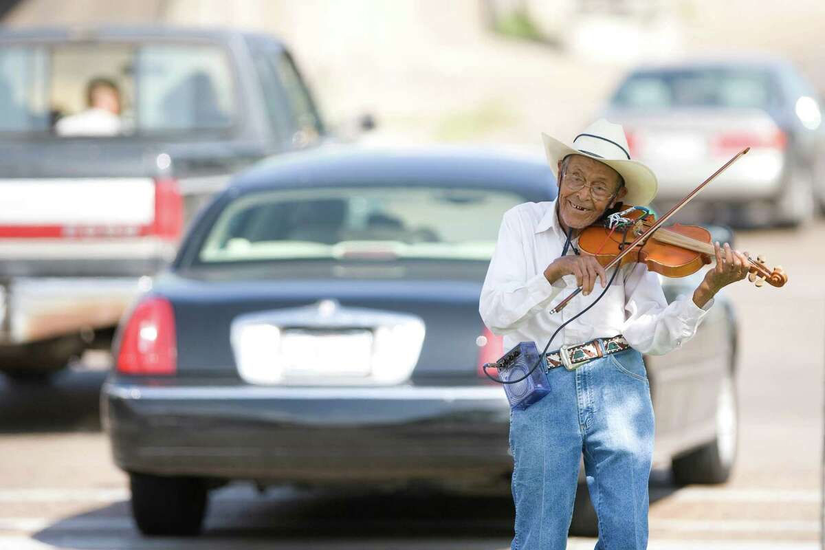 Luis Cruz, 86, of Houston, plays the violin for tips at the South Gulf Freeway and Woodridge intersection Tuesday, July 14, 2009, in Houston. Cruz says he like to sing and play, however, he uses the money to help his grandchildren make ends meet. ( Nick de la Torre / Chronicle )