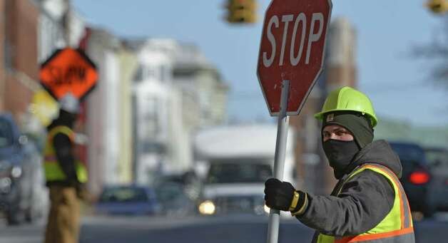 Time Warner sub contractor Jeremy Heines uses a face mask to ward off the cold temperatures Wednesday morning Jan. 29, 2014 as his crew controls the traffic on S. Lake Avenue in Albany, N.Y.        (Skip Dickstein / Times Union) Photo: Skip Dickstein