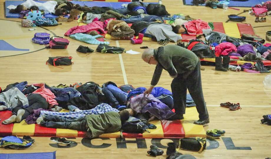 A teacher at E. Rivers Elementary school covers sleeping children in the gym Wednesday, Jan. 29, 2014 in Atlanta. A rare snowstorm left thousands across the U.S. South frozen in their tracks, with workers sleeping in their offices, students camping in their schools, and commuters abandoning cars along the highway to seek shelter in churches or even grocery stores.  (AP Photo/Atlanta Journal-Constitution, John Spink)  MARIETTA DAILY OUT; GWINNETT DAILY POST OUT; LOCAL TV OUT; WXIA-TV OUT; WGCL-TV OUT Photo: John Spink / Ajc, Associated Press