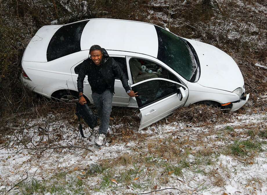 Jesse Hatcher limps away from his crash after he says another motorist caused him to lose control of his car and spin out off I-20 West near Conyers on Tuesday, Jan. 28, 2014, in Conyers, Georgia.   (AP Photo/Atlanta Journal-Constitution, Curtis Compton) Photo: Curtis Compton, Associated Press